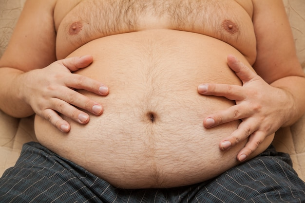 Fat belly of an obese man. the consequences of malnutrition