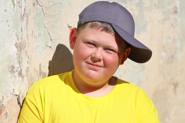 夏に壁に立って微笑んでいる黄色のtシャツと青い帽子の太った少年。高品質の写真
