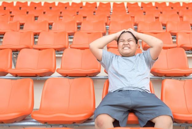 Толстяк возбуждает и сидит на футбольной трибуне