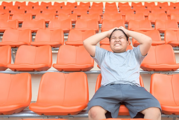 Fat boy is exciting and sit in the football grandstand