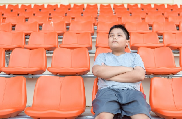 Fat boy is sitting in the football grandstand