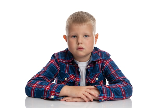 The fat boy is sitting at the table. schoolboy in a plaid shirt. back to school. isolated. close-up.