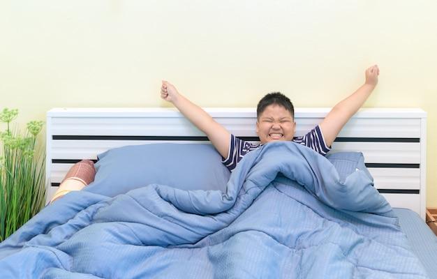 깨어 난 후 침대에서 스트레칭 뚱뚱한 소년, 프리미엄 사진
