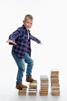 A fat boy walks up the stairs from the books. education and knowledge. full growth. vertical.