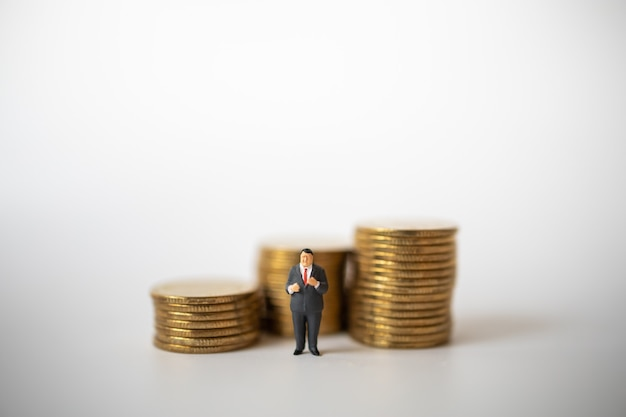 Fat businessman miniature figure people figure standing with stack of gold coins.
