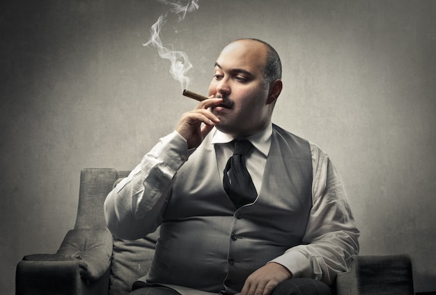Fat businessman smoking a cigar