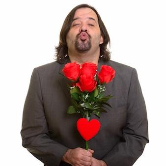 バレンタインデーの準備ができて赤いバラと心を保持しながら唇をパッカリングする太った白人実業家