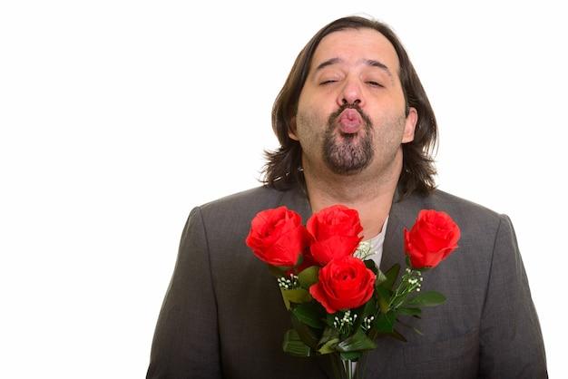 バレンタインデーの準備ができて赤いバラを保持しながら唇をパッカリングする太った白人実業家