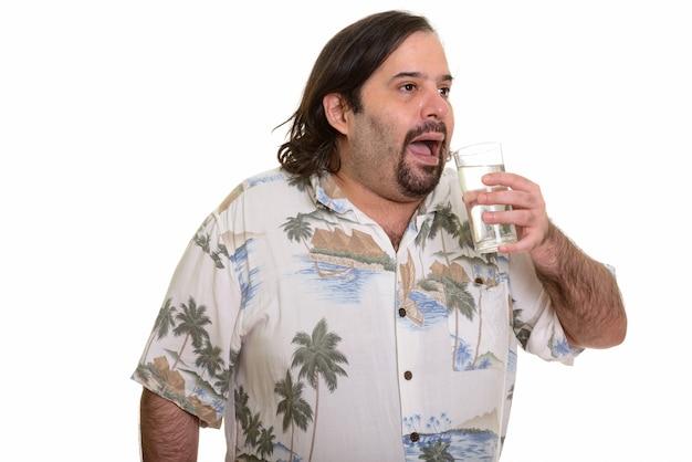 Толстый кавказский мужчина пьет стакан воды, глядя в сторону изолирован на белом