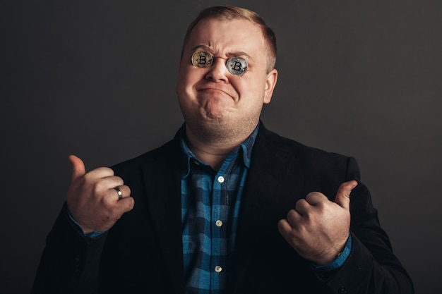 Толстый празднующий человек делает сумасшедшего face.crazy любителя биткойнов с золотой монетой на глазах