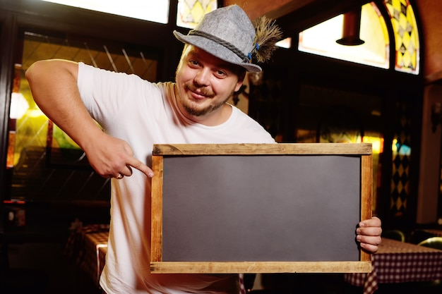 A fat cheerful man in a bavarian hat with a feather during the celebration of oktoberfest holds a sign or chalkboard in his hands