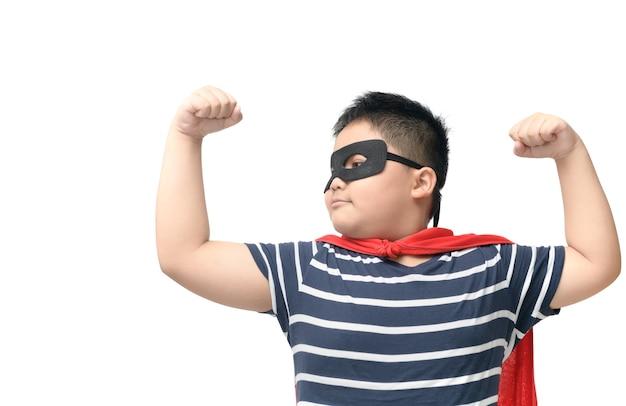 Жирный ребенок играет супергероя, изолированных на белом
