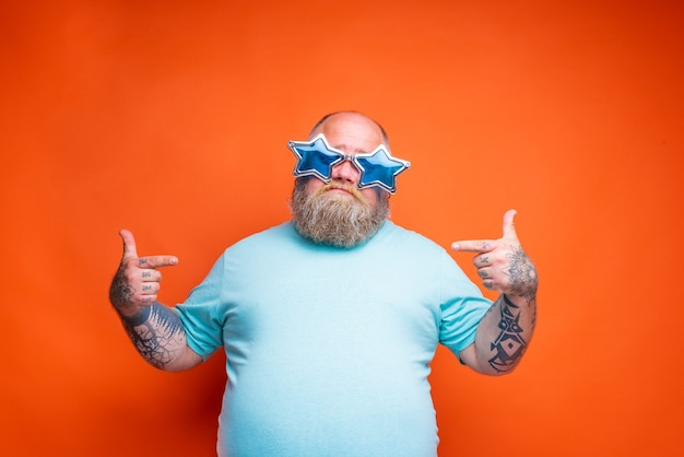 Fat doubter man with beard tattoos and sunglasses is uncertain for something
