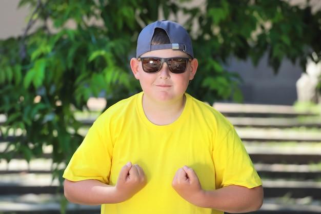 黄色のtシャツを着た太ったヨーロッパの少年は筋肉を示しています。高品質の写真