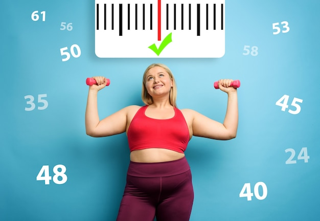 Fat girl does gym at home with satisfied expression because she decrease her weight. cyan background