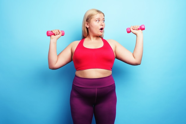 Fat girl does gym but is worried for something on cyan