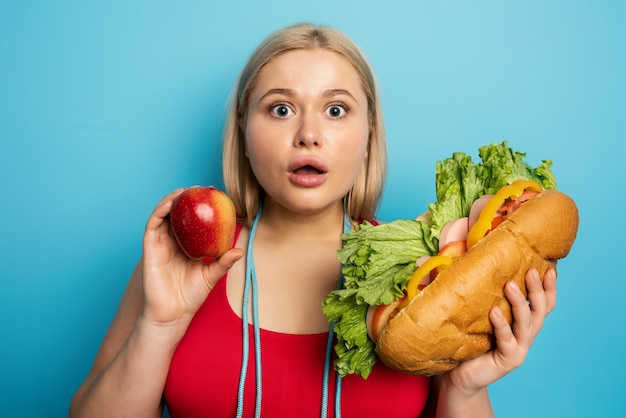 Fat girl does gym and want to eat a sandwich. concept of indecision and doubt