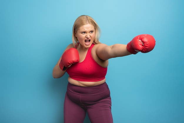 Fat girl in fitness suite does boxing.