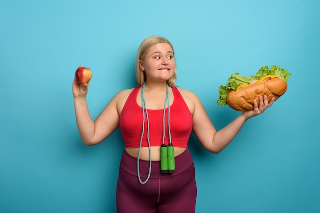 Fat girl is undecided to eat an apple or a big sandwich. cyan background