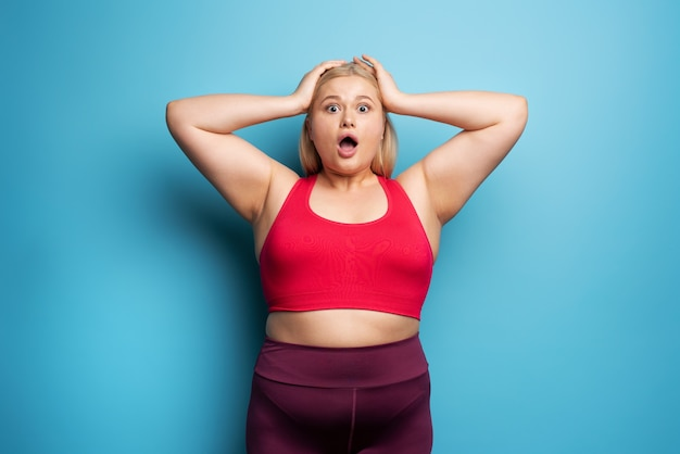Fat girl is worried because the scale marks a high weight.