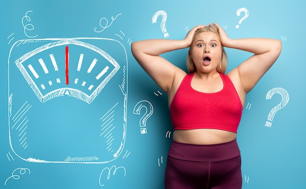 Fat girl is worried because the scale marks a high weight