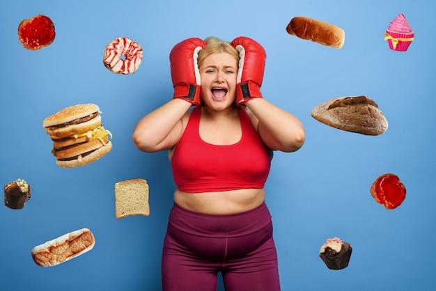 뚱뚱한 소녀는 살을 빼지 못하고 항상 먹는 것에 대해 생각하기 때문에 걱정합니다. 보라색 배경
