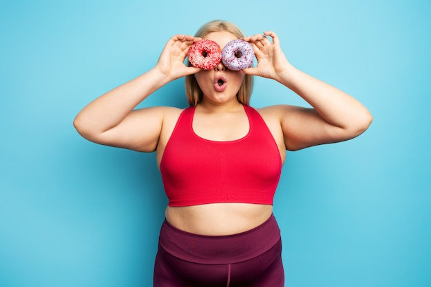 Fat girl thinks to eat donuts instead of does gym. concept of indecision and doubt