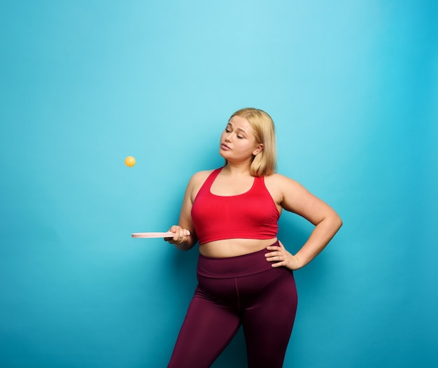 Fat girl tries to play with table tennis cyan background
