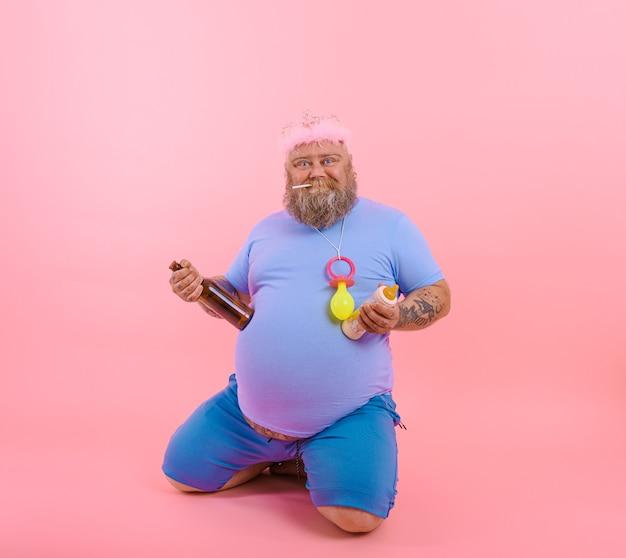 太った幸せな男は幸せな赤ちゃんのように振る舞いますが、ビールを飲みます