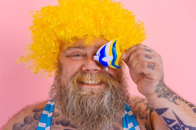 あごひげとサングラスで太った幸せな男は魚のおもちゃを楽しんでいます