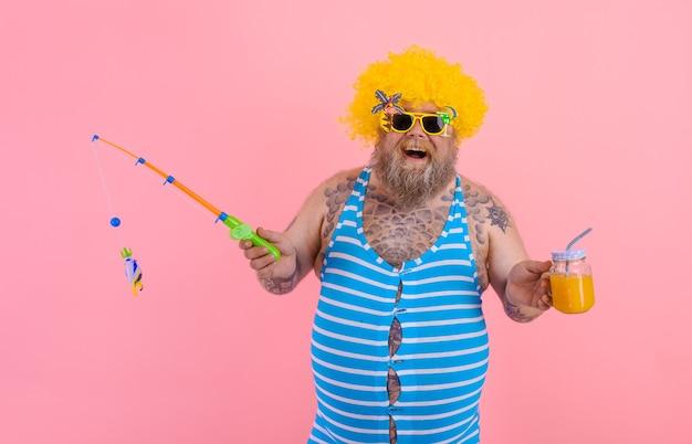 あごひげとサングラスで太った幸せな男は釣り竿を楽しんでいます
