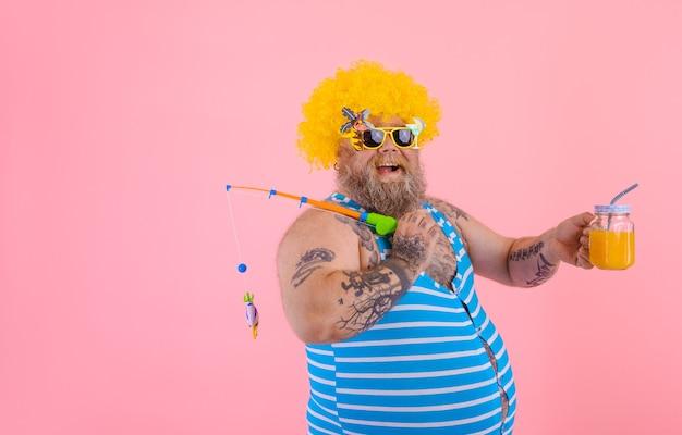 수염과 선글라스를 가진 뚱뚱한 행복한 남자는 낚싯대와 함께 즐거운 시간을 보낸다