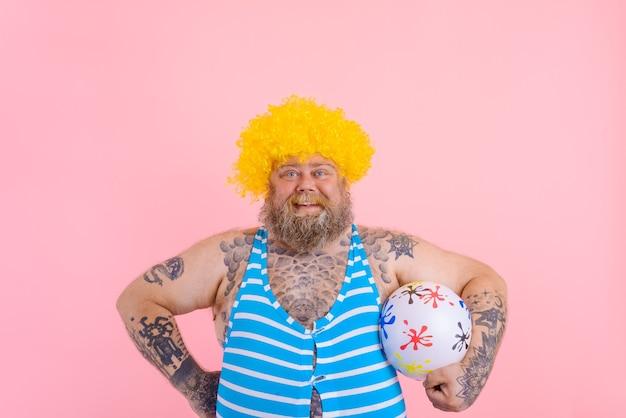 수염과 가발을 가진 뚱뚱한 행복한 남자가 공을 가지고 노는