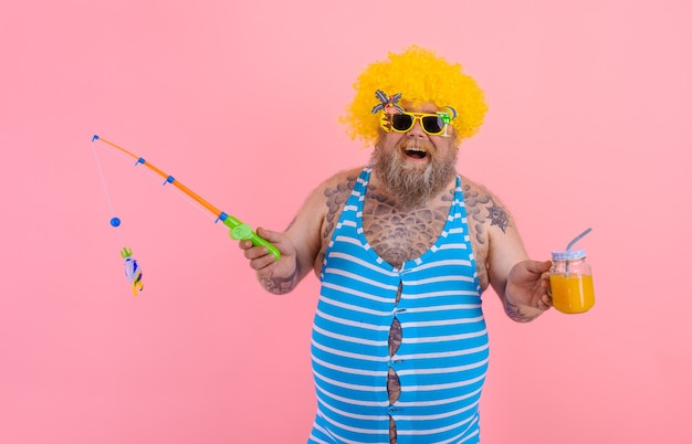 Fat happy man with beard and sunglasses have fun with the fishing pole