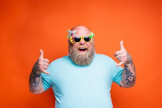 あごひげの入れ墨とサングラスで太った幸せな男は夏の準備ができています