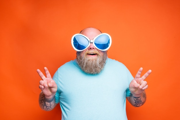 Fat happy man with beard tattoos and sunglasses makes the sign of victory with his hands