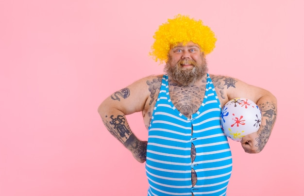 Fat happy man with beard and wig play with the ball