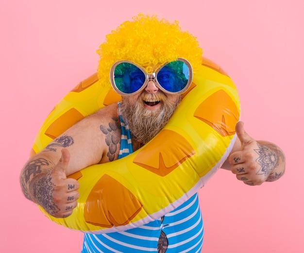머리에 가발을 쓴 뚱뚱한 행복한 남자는 도넛 구조원과 함께 수영할 준비가 되어 있습니다