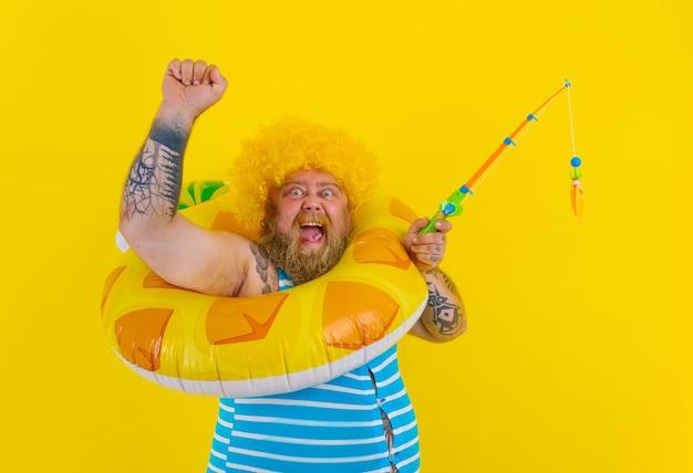 머리에 가발을 쓴 뚱뚱한 행복한 남자는 낚싯대를 가지고 노는다