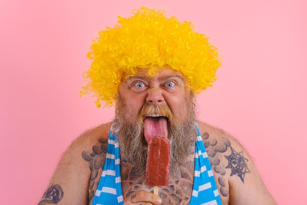 Fat hungry man with beard and wig eats a popsicle
