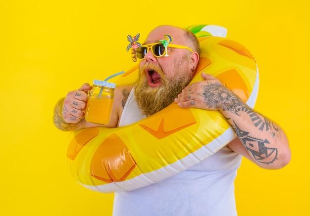 머리에 가발을 쓴 뚱뚱한 배고픈 남자가 도넛 구조원과 함께 수영할 준비가 되었습니다