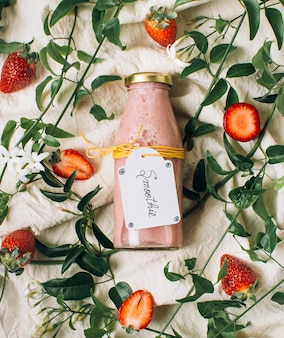 Fat lay pink smoothie next to strawberries