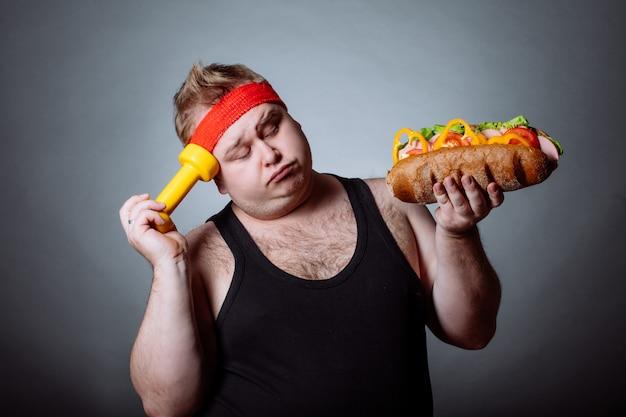 デブ男とハンバーガーとダンベルを保持