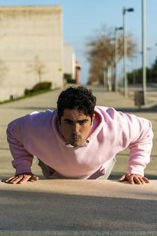 スポーツウェアの床で腕立て伏せをし、音楽を聴いている太った男