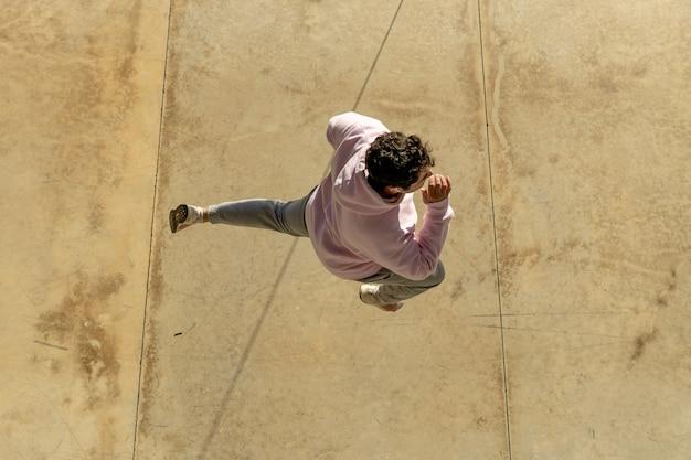 ピンクのスウェットシャツとスウェットパンツ、そして巻き毛に身を包んだ太った男