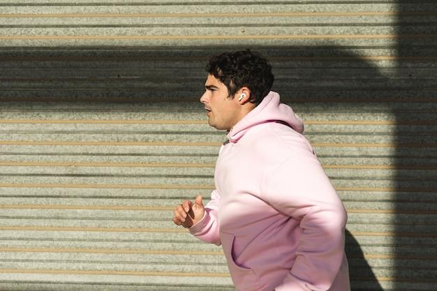 분홍색 운동복과 무선 헤드폰을 입은 뚱뚱한 남자가 스포츠를 한다