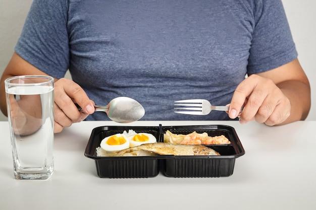 白いテーブルの上で食べ物の箱を食べる太った男。 covid-19患者のための在宅検疫の概念ベッドを待っている間の無症候性の軽度の症状
