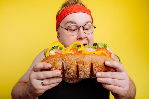 Fat man eating fast food hamburger