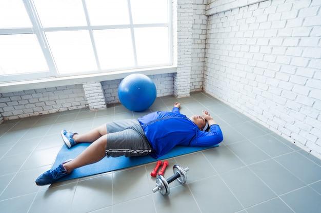 Толстяк занимается в тренажерном зале