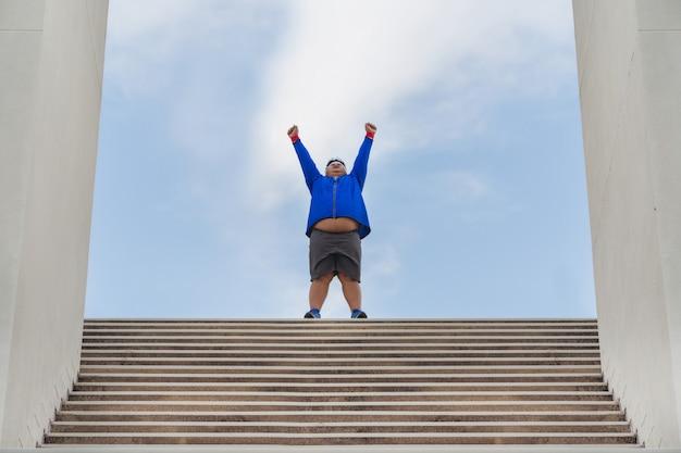 Толстяк упражняется по лестнице